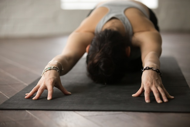 Yoga di pratica della giovane donna attraente posa del bambino