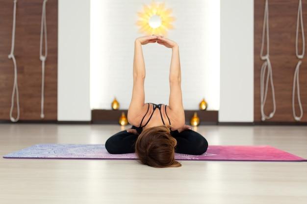 Yoga di pratica della giovane donna che allunga in palestra