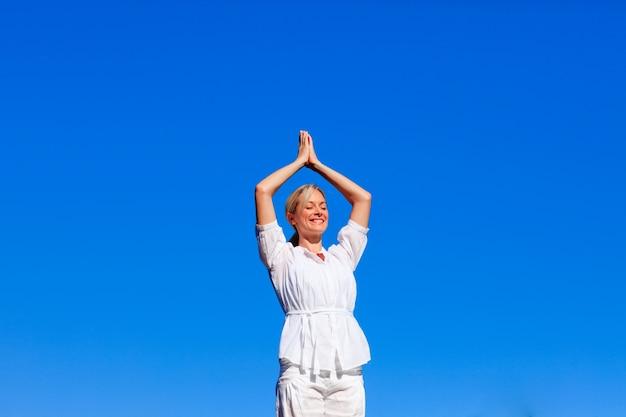 Yoga di pratica della giovane donna con copia-spazio