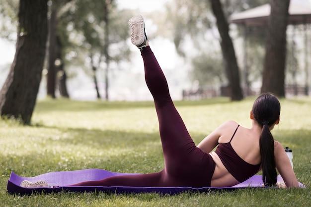 Yoga di pratica della giovane donna di vista posteriore all'aperto