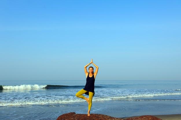Yoga di pratica della giovane donna ed esercizi di allungamento alla spiaggia dell'oceano di estate