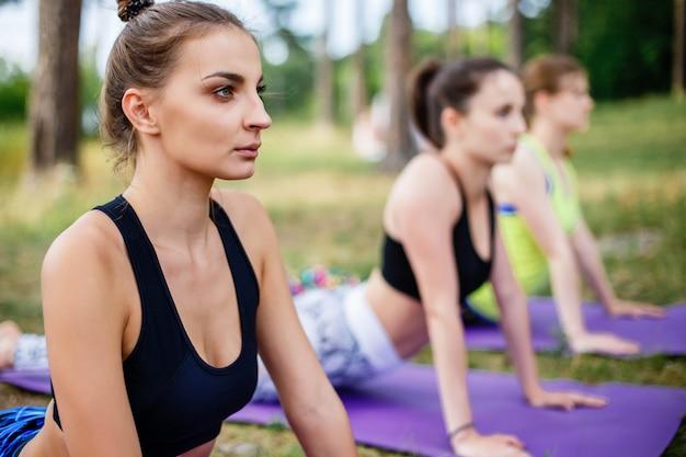 Yoga di pratica della giovane donna in parco