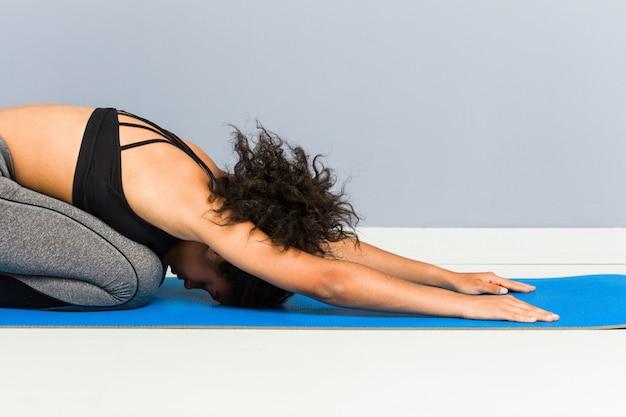 Yoga di pratica della giovane donna sportiva afroamericana che si trova facendo uso di una stuoia