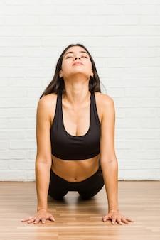 Yoga di pratica della giovane donna sportiva araba sul pavimento