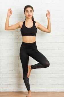 Yoga di pratica della giovane donna sportiva araba