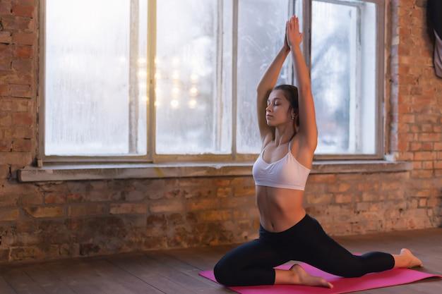 Yoga di pratica della giovane donna sportiva vicino alla finestra