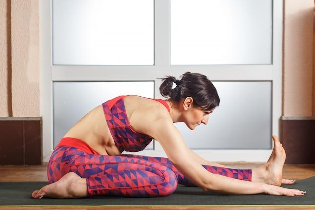 Yoga di pratica della giovane donna sportiva