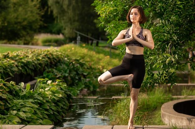 Yoga di pratica della giovane donna su un ponte vicino ad un lago decorativo nel parco