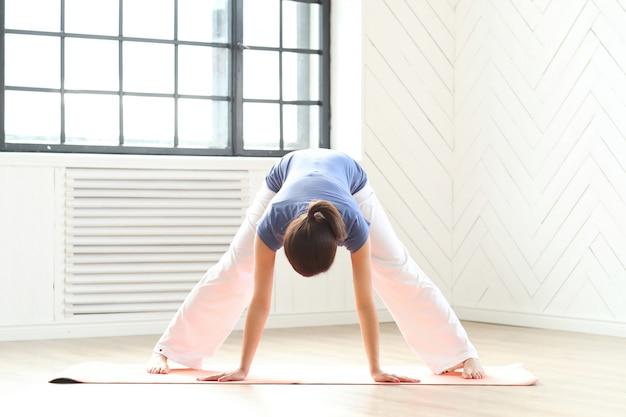 Yoga di pratica della giovane donna su una stuoia di yoga
