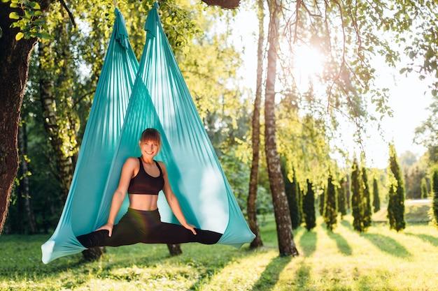 Yoga di pratica della mosca della bella donna all'albero
