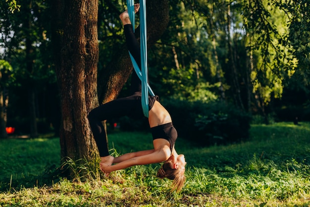 Yoga di pratica della mosca della giovane donna all'albero
