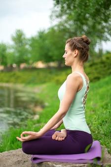 Yoga donna che pratica lezione di yoga, respirazione, meditazione, esercizio fisico ardha padmasana, mezza posa di loto con gesto mudra, primo piano in estate sulla natura sullo sfondo di acqua