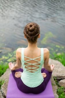 Yoga donna pratica lezione di yoga, respirazione, meditazione, esercizio fisico ardha padmasana, mezza posa di loto con gesto mudra, primo piano in estate sulla natura contro l'acqua