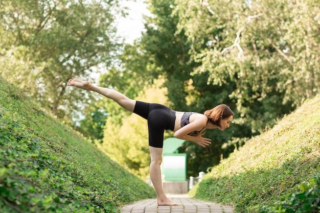 Yoga facente sola della giovane donna su un vicolo del parco un giorno di estate soleggiato.
