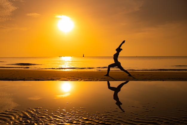 Yoga ragazza pratica yoga sulla spiaggia alba mattina giorno