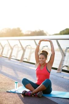 Yoga sul ponte. donna che sorride mentre sedendosi sulla stuoia di sport e facendo yoga sul ponte
