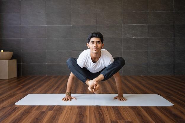 Yogi con esperienza che fanno variazione di posa della lucciola in palestra