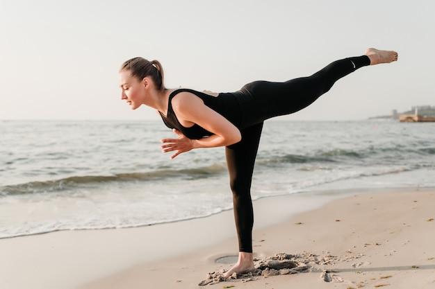 Yogi donna in piedi su una gamba sola in asana yoga vicino oceano sulla sabbia