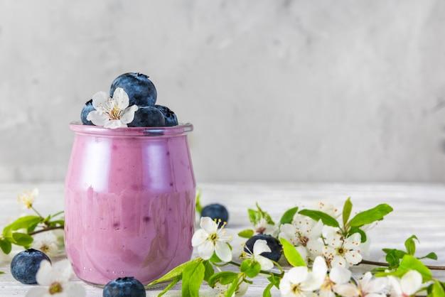 Yogurt ai mirtilli in un bicchiere servito con mirtilli freschi e fiori di ciliegio in fiore primaverile