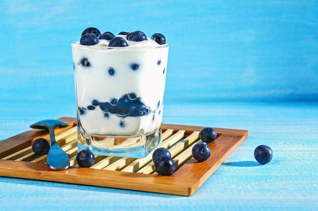 Yogurt con bacche di prugnolo blu in un bicchiere. dolce alla bacca