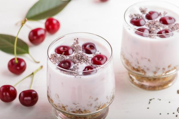 Yogurt con ciliegie, semi di chia e muesli in vetro con un cucchiaio di legno. vista laterale.