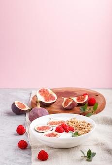 Yogurt con lamponi, muesli e fichi nel piatto bianco su uno sfondo grigio e rosa