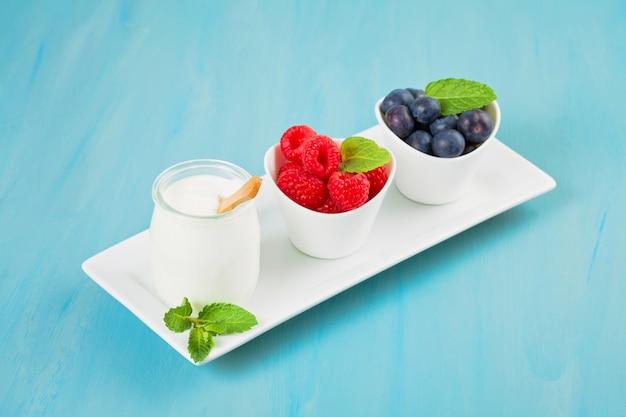 Yogurt con mirtilli e raspberies - concetto di salute e dieta. colazione sana equilibrata