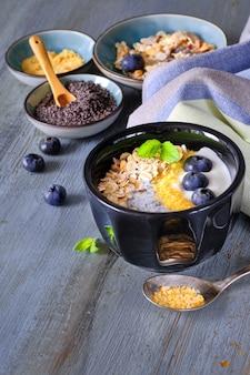Yogurt con muesli, mirtilli, semi di papavero, menta e cornflakes schiacciati serviti in una ciotola nera lucida