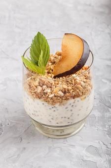 Yogurt con prugne, semi di chia e muesli in un bicchiere