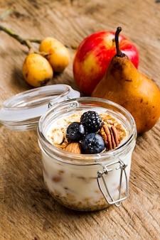 Yogurt dell'angolo alto con i dadi e i frutti di frutti della foresta nera