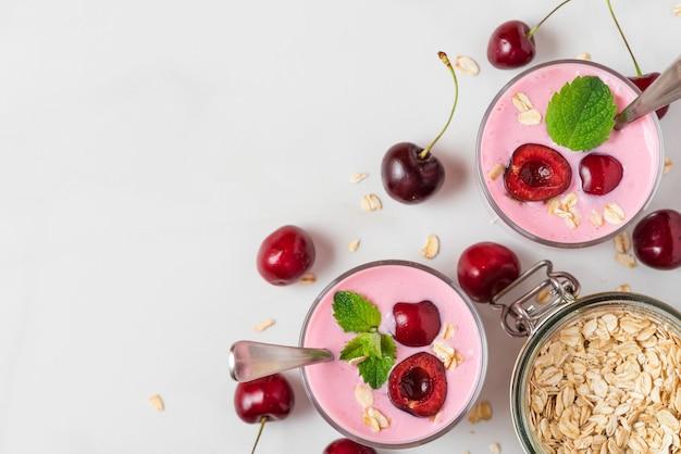 Yogurt della ciliegia con le bacche, l'avena e la menta fresche in vetri con i cucchiai su bianco. colazione salutare. vista dall'alto