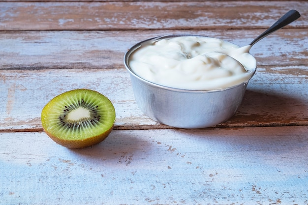 Yogurt e kiwi naturali sulla tavola di legno