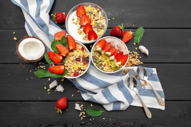 Yogurt fatto in casa con vista dall'alto di muesli, frutta e cocco su fondo di legno