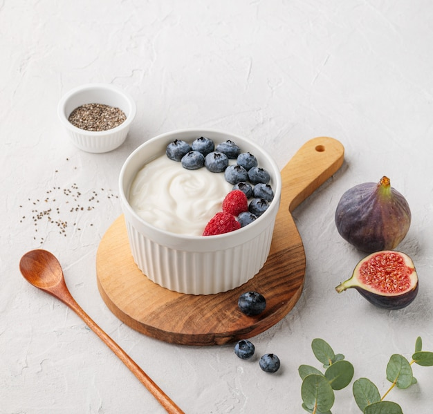 Yogurt fermentato superfood sano naturale con mirtillo, fichi, semi di chia e lampone in ciotola bianca sul tavolo grigio chiaro. l'immagine è lo spazio della copia e la vista dall'alto