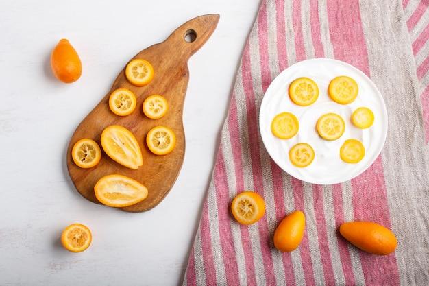 Yogurt greco con pezzi di kumquat in un piatto bianco su un fondo di legno bianco