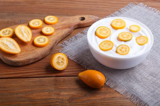 Yogurt greco con pezzi di kumquat in un piatto bianco su un fondo di legno marrone