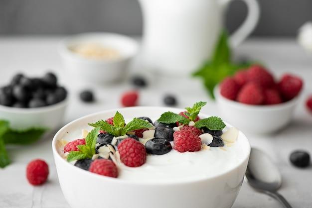 Yogurt greco fresco con mirtilli, lamponi e menta