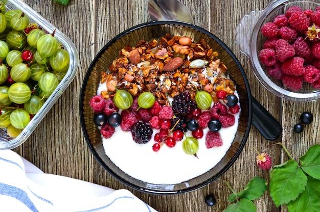 Yogurt, muesli e frutti di bosco freschi in una ciotola su un tavolo di legno