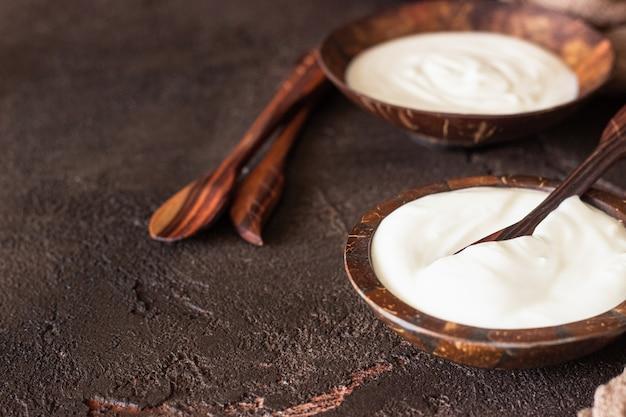 Yogurt naturale fatto in casa biologico in ciotole di guscio di cocco prodotto a base di latte fermentato fresco e naturale