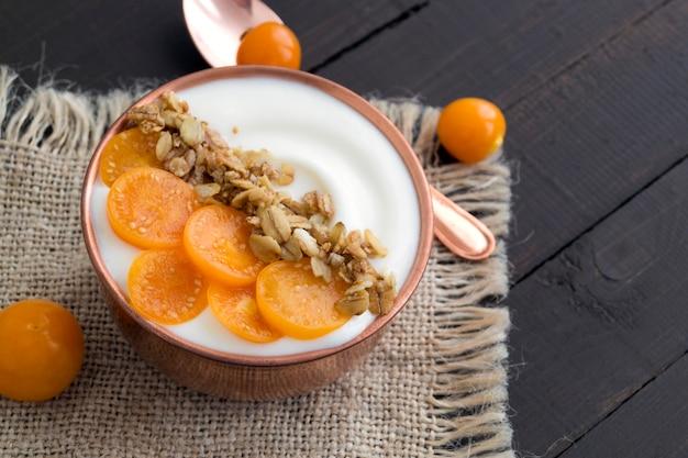 Yogurt naturale fatto in casa con macinata di ciliegia su un tavolo di legno.