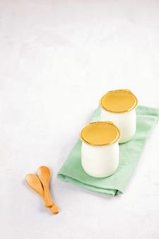 Yogurt naturale industriale in lattine di plastica. concetto di colazione sana e veloce