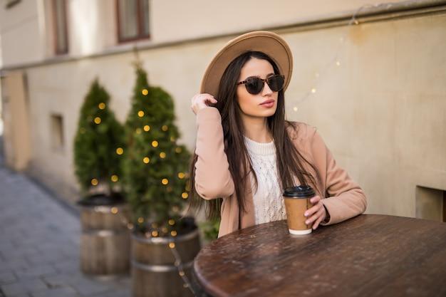 Yound modella è seduta sul tavolo di abiti da caffè in abiti casual occhiali da sole scuri con una tazza di caffè