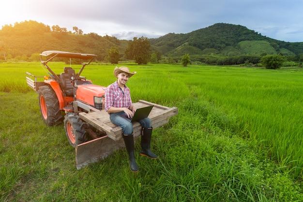 Young farmer ha registrato una crescita della produttività seduta su un trattore.