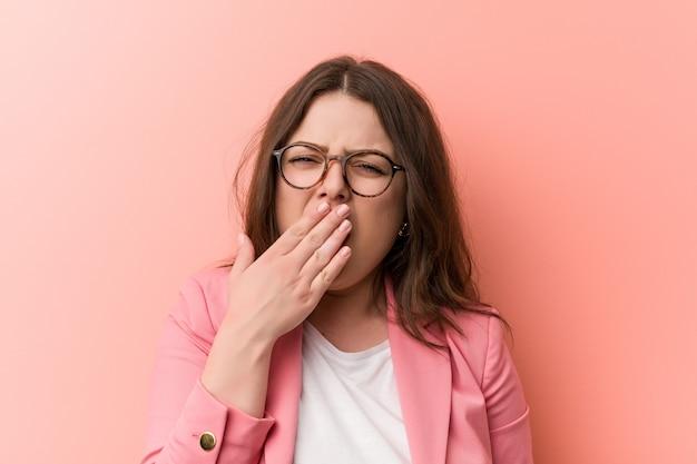 Young plus size business caucasica donna che sbadiglia mostrando gesto stanco che copre la bocca con lui mano.