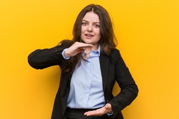 Young plus size caucasica donna d'affari in possesso di qualcosa con entrambe le mani, presentazione del prodotto.