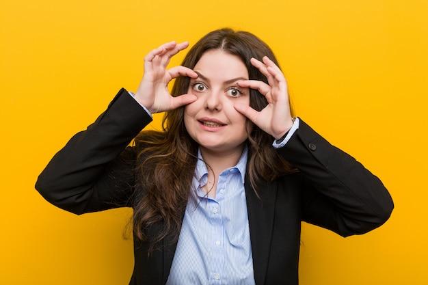 Young plus size donna d'affari caucasica tenendo gli occhi aperti per trovare un'opportunità di successo.