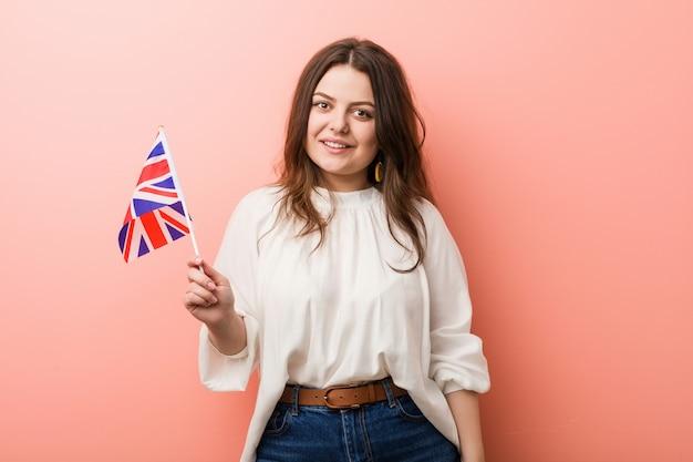 Young plus size donna formosa in possesso di una bandiera del regno unito felice, sorridente e allegra.
