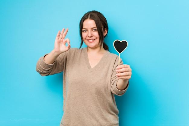 Young plus size donna formosa tenendo una forma di cuore allegro e fiducioso mostrando gesto ok.