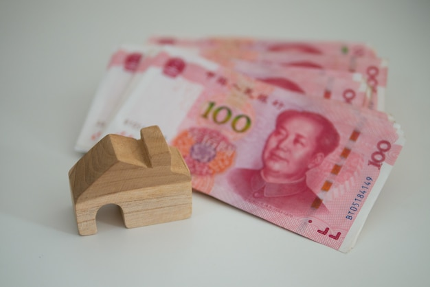 Yuan cinese di valuta della banconota e blocco di casa di legno per il concetto di affari della terra e della proprietà