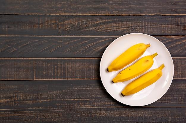 Yummy banane sul piatto bianco su un tavolo di legno